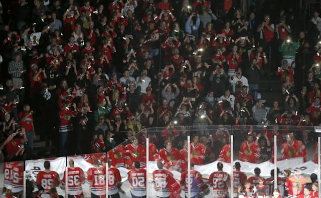The Chicago Blackhawks are reflected in the glass as they carry out the Stanley Cup Championship banner during ceremonies before an NHL hockey game between the Blackhawks and the Washington Capitals, Tuesday, Oct. 1, 2013, in Chicago. (AP Photo/Charles Rex Arbogast)