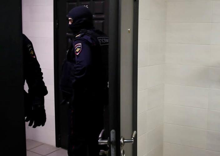 Law enforcement officers stand outside an apartment of Russian opposition leader Alexei Navalny in Moscow