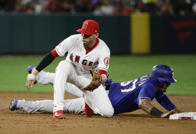 Texas Rangers' Ronald Guzman, right, dives back to second as Los Angeles Angels shortstop Andrelton Simmons waits for the pickoff throw during the third inning of a baseball game in Anaheim, Calif., Tuesday, Sept. 25, 2018. (AP Photo/Chris Carlson)