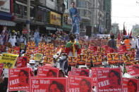 Anti-coup protesters hold up posters with images of deposed Myanmar leader Aung San Suu Kyi during a rally near the Mandalay Railway Station in Mandalay, Myanmar Monday, Feb. 22, 2021. A call for a Monday general strike by demonstrators in Myanmar protesting the military's seizure of power has been met by the ruling junta with a thinly veiled threat to use lethal force, raising the possibility of major clashes. (AP Photo)