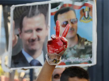 A supporter of Syria's President Bashar al-Assad gestures while wearing a glove with fake blood in front of pictures of Assad during a sit-in near the U.S. embassy in Awkar, north of Beirut, against potential U.S. strikes on Syria September 6, 2013. REUTERS/Mohamed Azakir