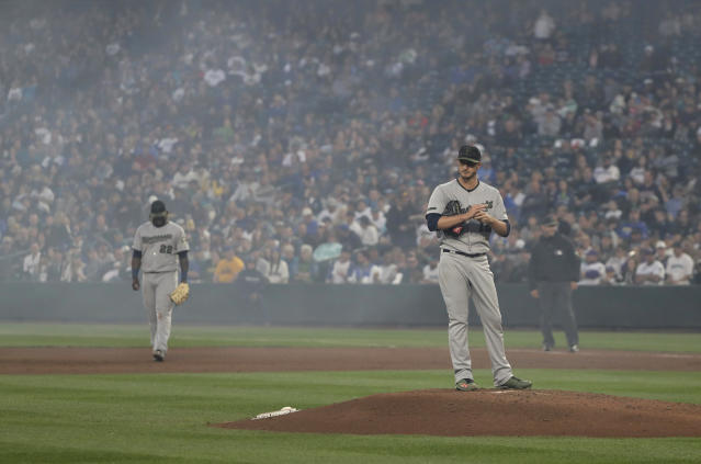 Minnesota Twins starting pitcher Jake Odorizzi stands on the mound as smoke from fireworks at Safeco Field clears behind him after Seattle Mariners' Jean Segura hit a solo home run during the sixth inning of a baseball game Saturday, May 26, 2018, in Seattle. (AP Photo/Ted S. Warren)