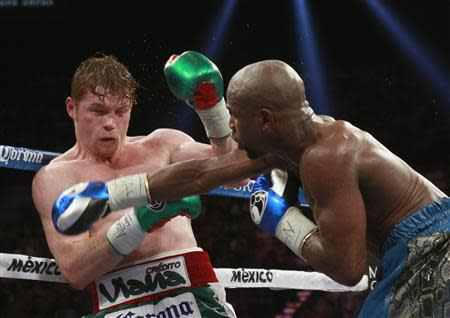 Canelo Alvarez (L) of Mexico takes a punch from Floyd Mayweather Jr. of the U.S. during their WBC/WBA 154-pound title fight at the MGM Grand Garden Arena in Las Vegas, Nevada, September 14, 2013. REUTERS/Steve Marcus