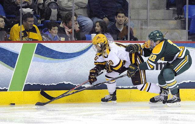 Minnesota's Kelly Terry, left, and Clarkson's Renata Fast fight for a loose puck during the first period of an NCAA college hockey game in the finals of the women's Frozen Four in Hamden, Conn., Sunday, March 23, 2014. (AP Photo/Fred Beckham)