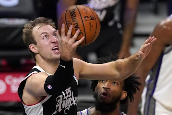 Los Angeles Clippers guard Luke Kennard, left, shoots as Sacramento Kings forward Marvin Bagley III watches during the first half of an NBA basketball game Sunday, Feb. 7, 2021, in Los Angeles. (AP Photo/Mark J. Terrill)