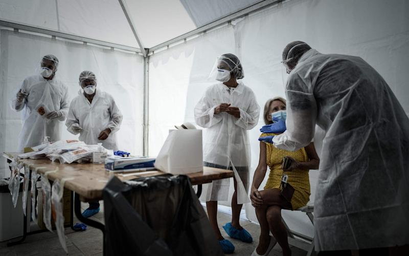 A woman speaks with medical staff during a COVID-19free screening operation outside the Arcachon railway station - PHILIPPE LOPEZ/AFP