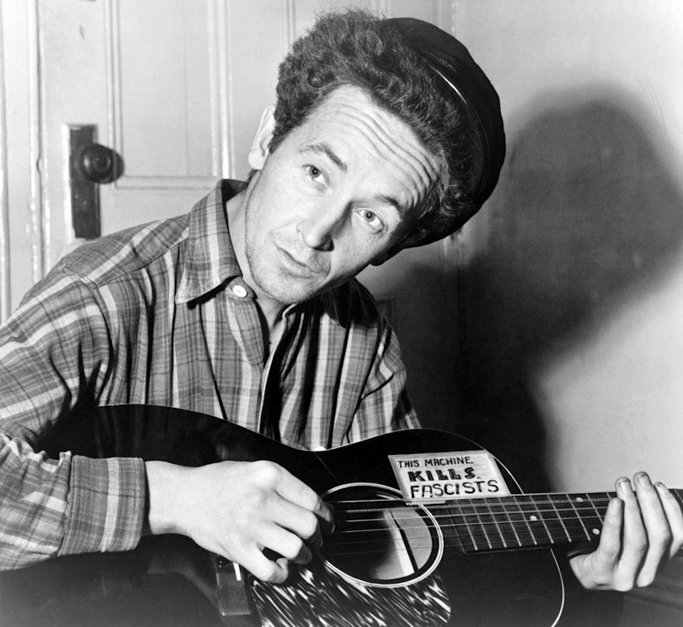 """Woody Guthrie holding his """"this machine kills fascists"""" guitar"""