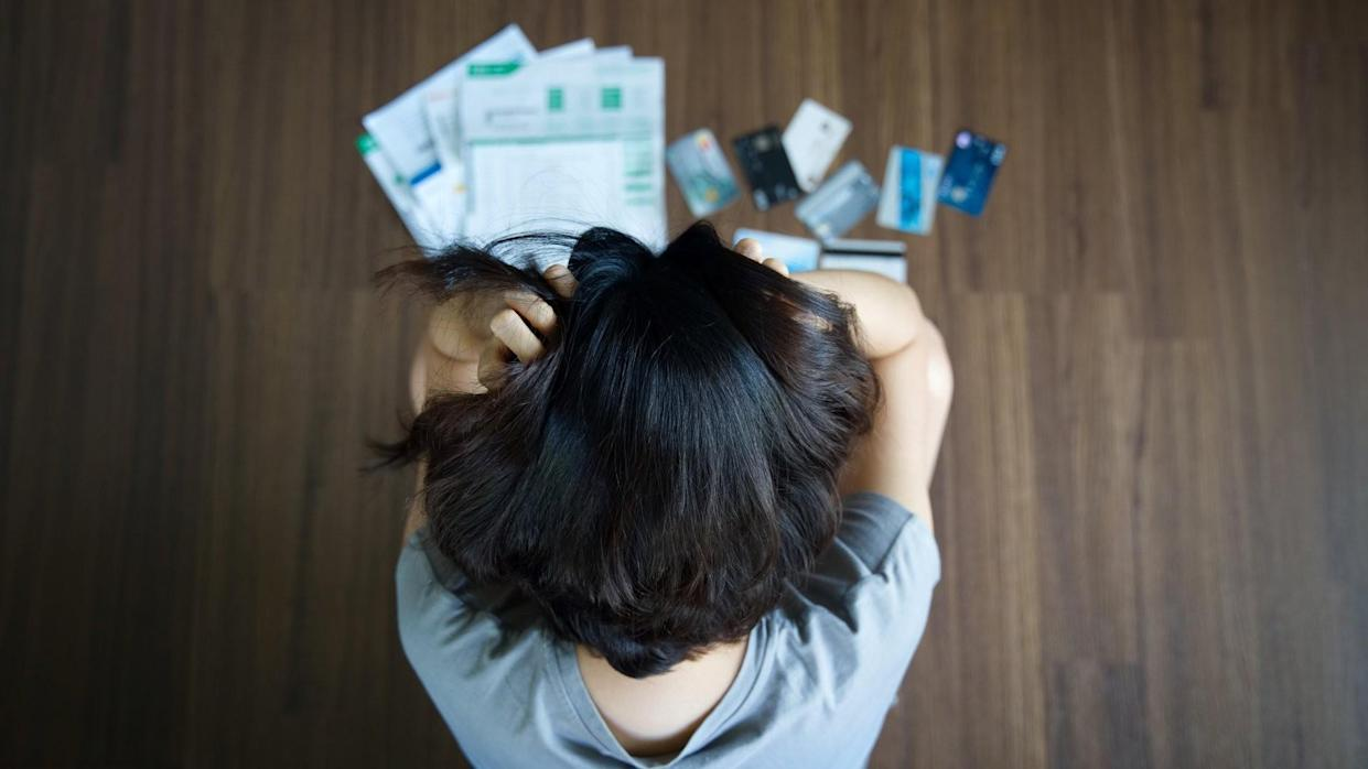 Woman with credit cards and bills spread on the floor