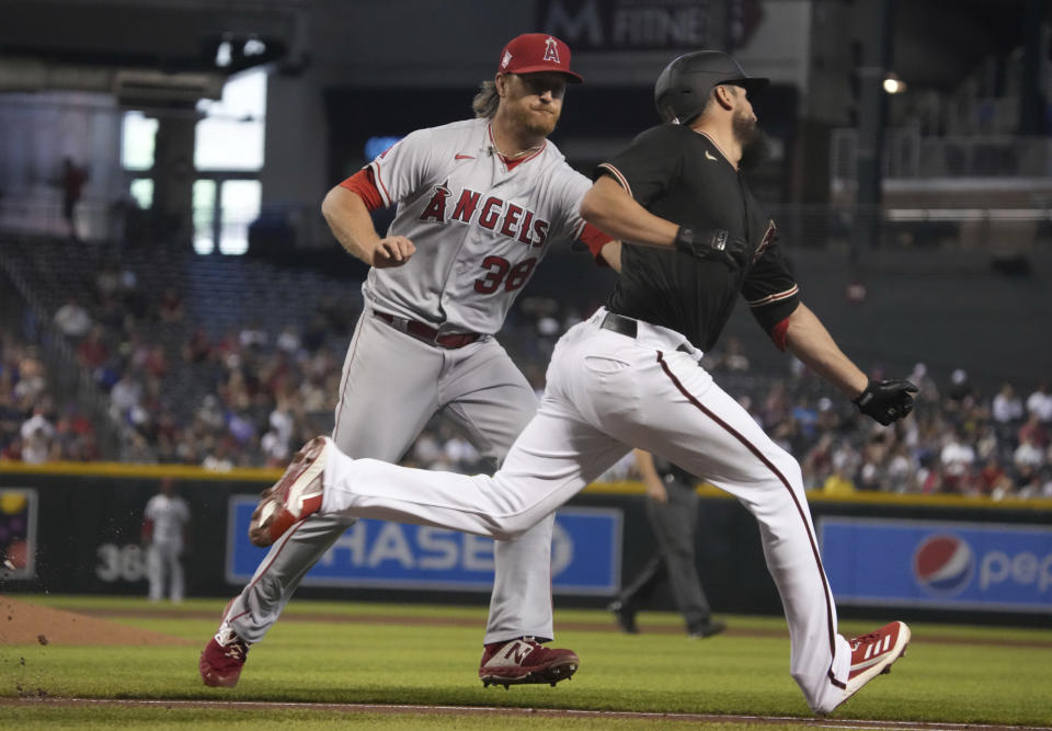 Arizona Diamondbacks' Caleb Smith gets tagged out by Los Angeles Angels' Alex Cobb (38) after laying down a sacrifice bunt in the third inning during a baseball game, Saturday, June 12, 2021, in Phoenix. (AP Photo/Rick Scuteri)