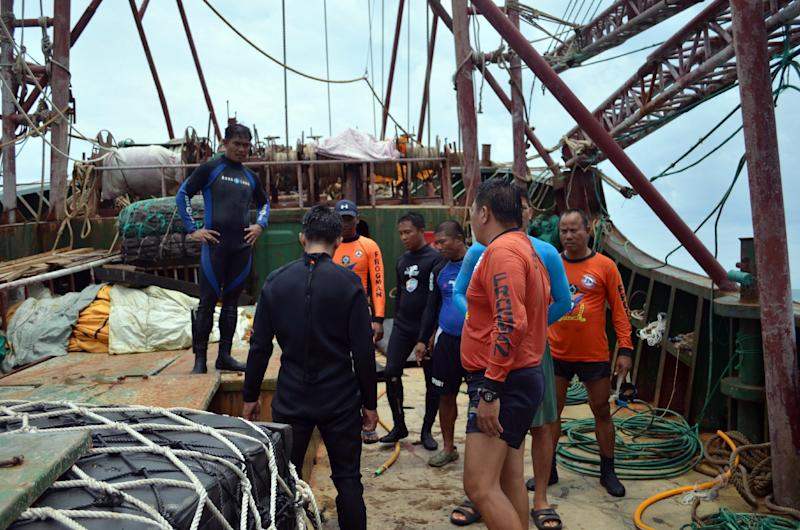 Photo released on April 10, 2013 shows Philippine Coast Guard personnel inspecting the Chinese fishing vessel that ran aground off Tubbataha reef in Palawan island, western Philippines (AFP Photo/Philippine Coast Guard)