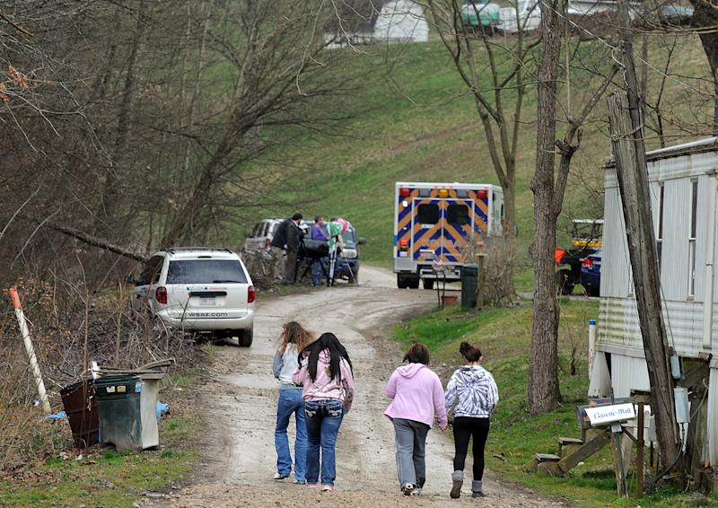 """FILE - In this April 1, 2013 file photo, Friends and neighbors walk up and down the gravel road leading to Shain Gandee's home in Sissonville, W.Va. Gandee, star of the MTV show """"Buckwild""""; his uncle, David Gandee; and Donald Robert Myers were found dead in the family's Ford Bronco Monday morning. (AP Photo/The Charleston Gazette, Chip Ellis, File)"""