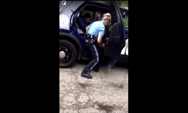A police officer in Michigan was filmed striking a teenage girl in the back of a squad car. (Screenshot: Twitter/ms_nette09)