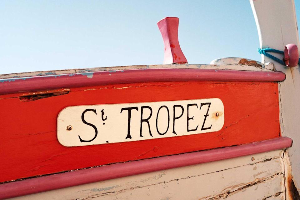 A read and white boat with St Tropez painted in black