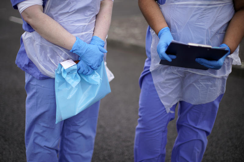 WOLVERHAMPTON, ENGLAND - MARCH 12: A NHS nurse holds a Coronavirus testing kit as she speaks to the media at a drive through Coronavirus testing site in a car park on March 12, 2020 in Wolverhampton, England. The National Health Service facility has been set up in a car park to allow people with NHS referrals to be swabbed for Covid-19. (Photo by Christopher Furlong/Getty Images)