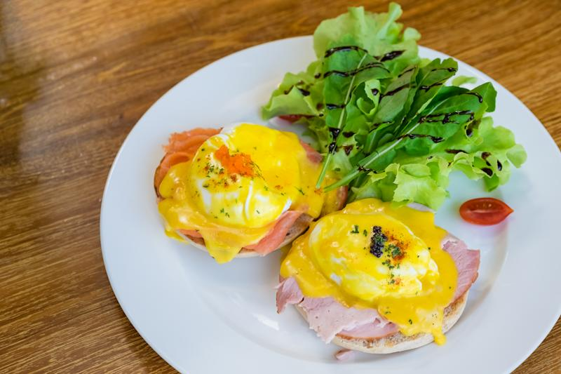 closeup dish of egg benedict with meat and bread on wood table background