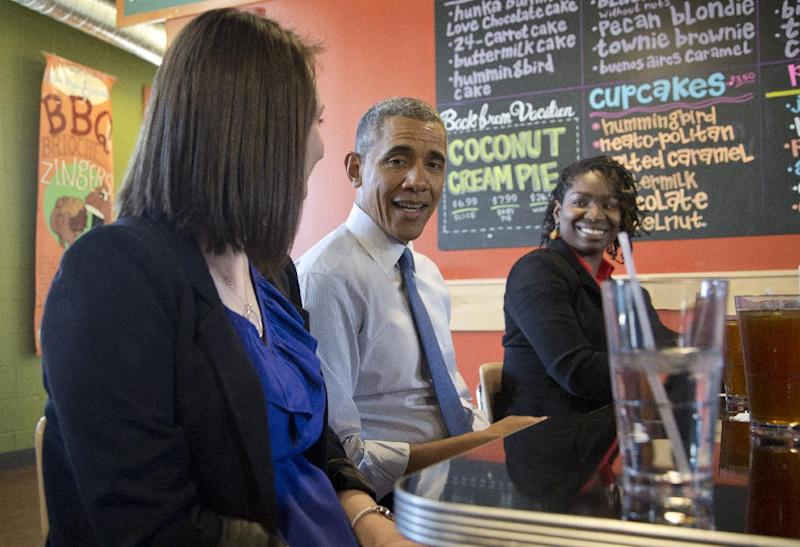 President Barack Obama sits between Mira Friedlander, a 22 year old senior at the University of Michigan, left, and Aisha Turner, 36, a mother of three who has worked for nearly two decades as a server as he has lunch at Zingerman's Deli in Ann Arbor, Mich., Wednesday, April 2, 2014, before speaking at the University of Michigan about his proposal to raise the national minimum wage. (AP Photo/Carolyn Kaster)