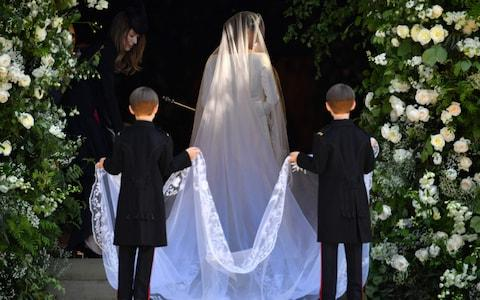 US actress Meghan Markle arrives for her wedding ceremony. Page boys Brian and John Mulroney are pictured holding her train - Credit: AFP