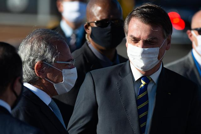 BRASILIA, BRAZIL - MAY 12: President of Brazil Jair Bolsonaro wearing a face mask talks to Paulo Guedes, Minister of Economy, as they greet supporters before flag ceremony amidst the coronavirus (COVID-19) pandemic at the Palácio do Alvorada on May 12, 2020 in Brasilia. Brazil has over 168,000 confirmed positive cases of Coronavirus and 11,519 deaths. (Photo by Andressa Anholete/Getty Images)