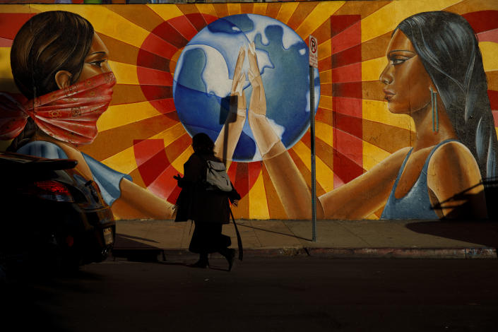 """A pedestrian walks past the mural """"¡Resiste!"""" by Nanibah Chacon outside Self-Help Graphics & Art, Inc. in Boyle Heights, Los Angeles. (Photo: Patrick T. Fallon for Yahoo News)"""