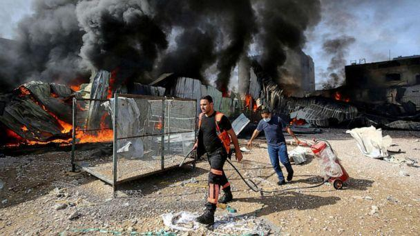 PHOTO: Palestinian firefighters douse a fire at a sponge factory after it was hit by Israeli artillery shells, according to witnesses, in the northern Gaza Strip, on May 17, 2021.  (Ashraf Abu Amrah/Stringer/Reuters)