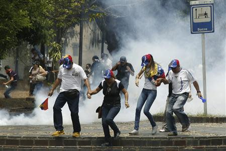 Anti-government protesters run from tear gas during protest against Maduro's government in San Cristobal
