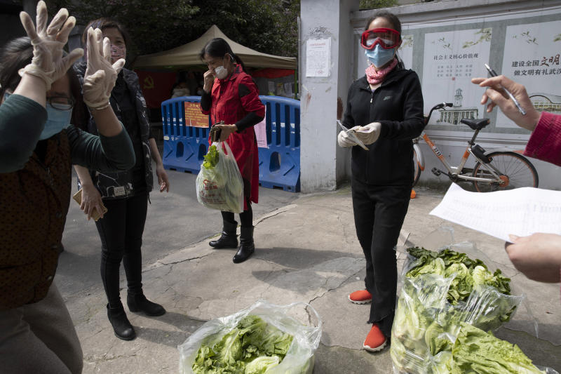 In this Monday, April 6, 2020, photo, a resident in red collects her vegetable from other resident volunteers in Wuhan in central China's Hubei province. Some farmers are finding temporary outlets for sales through volunteers in Wuhan helping the elderly and other vulnerable people get food supplies. They buy direct from farmers and arrange delivery to apartment complexes. (AP Photo/Ng Han Guan)