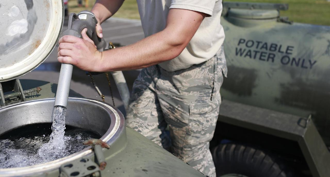 Ohio Air National Guard Senior Airman Nick Wander fills a 400 gallon military water buffalo with fresh drinking water, Sunday, Aug. 3, 2014, at Woodward High School in Toledo, Ohio. More tests are needed to ensure that toxins are out of Toledo's water supply, the mayor said Sunday, instructing the 400,000 people in the region to avoid drinking tap water for a second day. Toledo officials issued the warning early Saturday after tests at one treatment plant showed two sample readings for microsystin above the standard for consumption, possibly because of algae on Lake Erie. (AP Photo/Haraz N. Ghanbari)