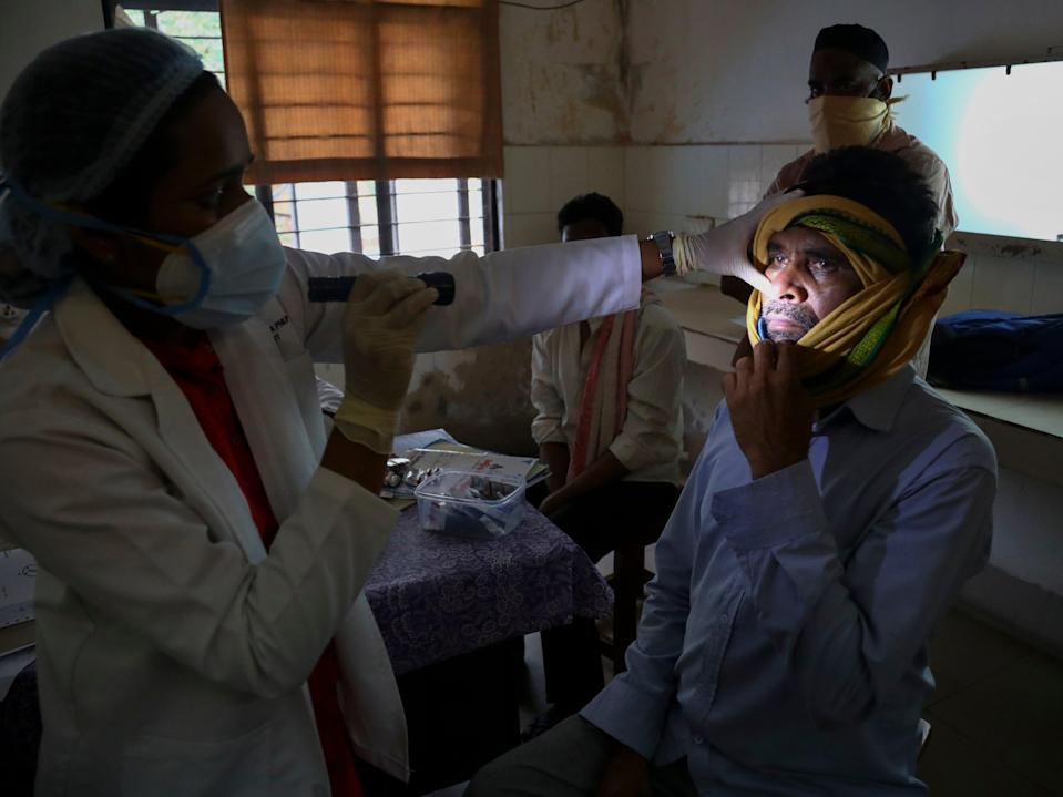 <p>A doctor checks a man who recovered from Covid-19 and is now infected with black fungus at the Mucormycosis ward of a hospital in Hyderabad, India</p> (AP)