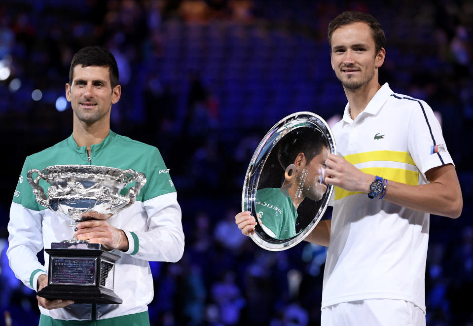Serbia's Novak Djokovic, left, holds the Norman Brookes Challenge Cup after defeating Russia's Daniil Medvedev, right, in the men's singles final at the Australian Open tennis championship in Melbourne, Australia, Sunday, Feb. 21, 2021.(AP Photo/Andy Brownbill)