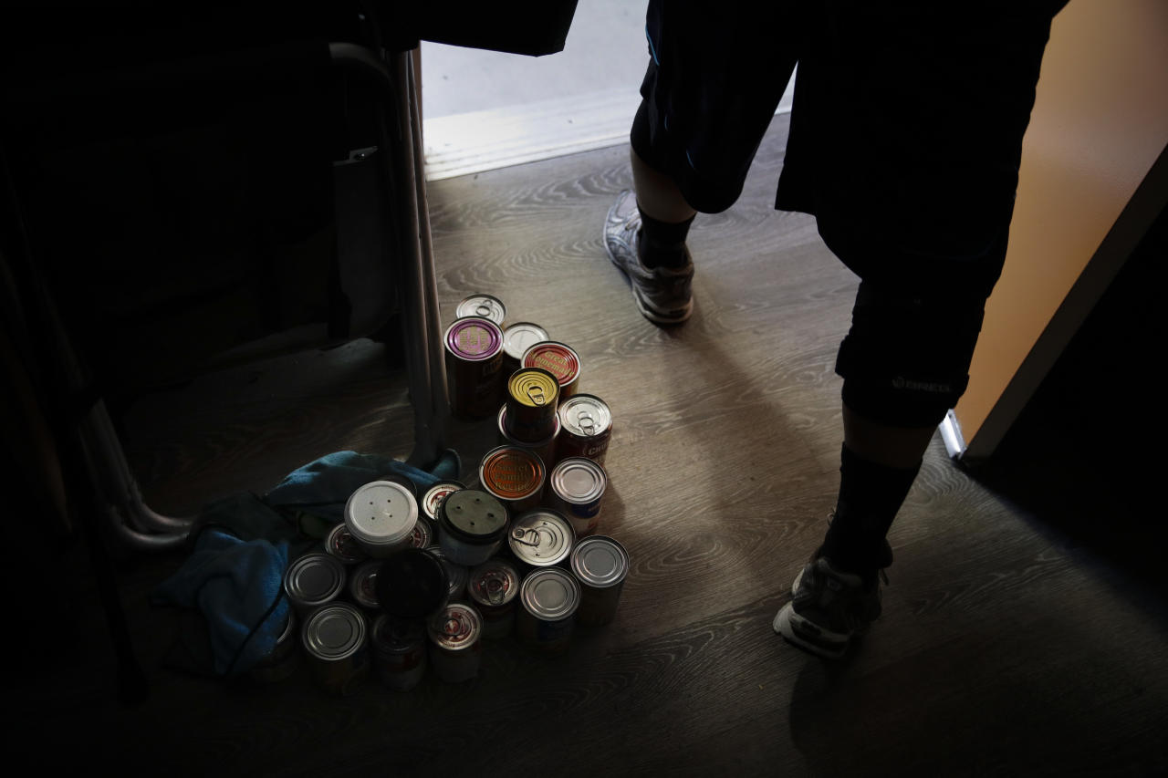 In this Monday, Aug. 14, 2017 photo, donated canned goods are stacked on the apartment floor as Iraq war veteran Vernon Poling, 44, walks out of his apartment for grocery shopping in Midway City, Calif. Poling was homeless for seven months before he found temporary housing in the area. He was living there when he found out about Potter's Lane, an apartment complex made out of recycled shipping containers just for homeless veterans, believed to be the first of its kind in the nation. (AP Photo/Jae C. Hong)