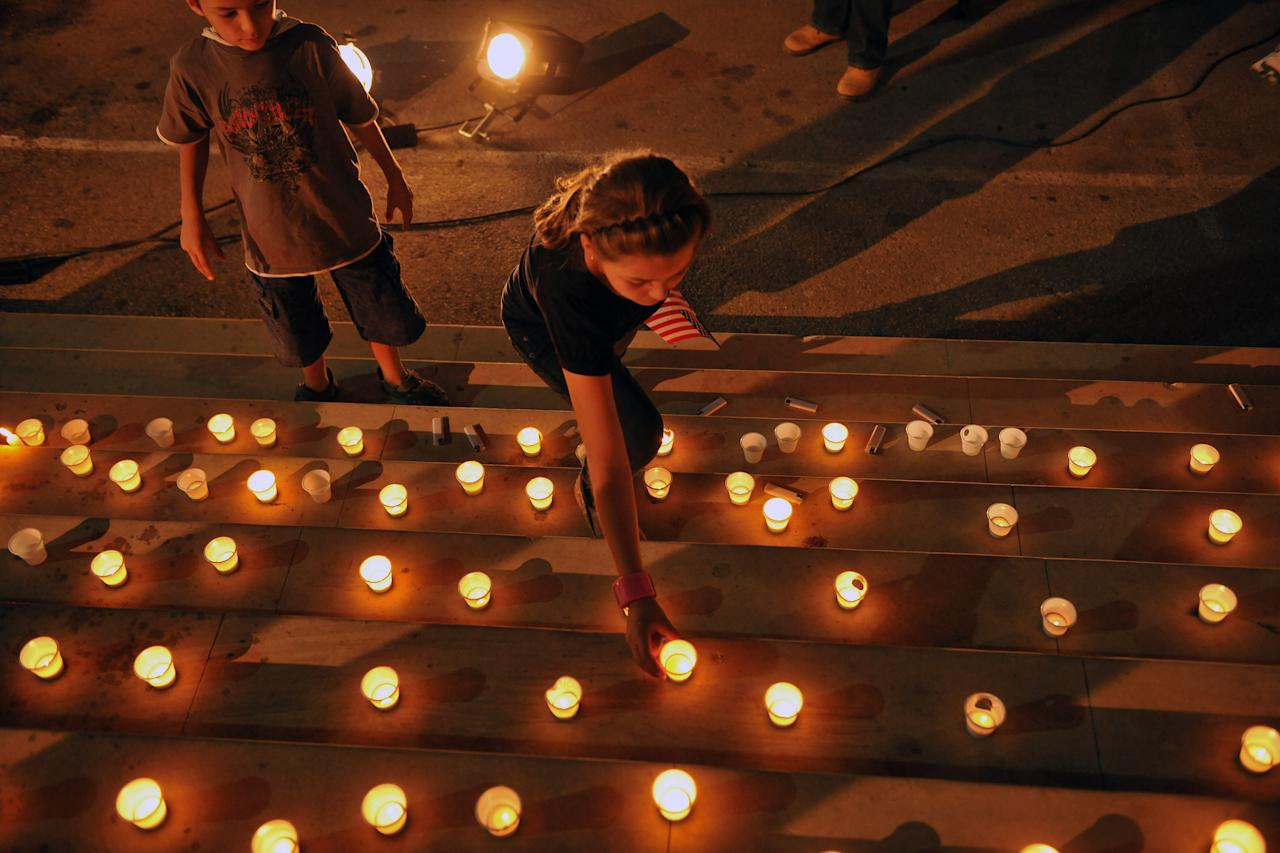 Kosovo youth lights a candles to mark the 10th anniversary of the 9/11 terror attacks on the United States, in capital Pristina, Kosovo, on Sunday, Sept. 11, 2011. ( AP Photo / Visar Kryeziu )