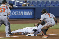 Miami Marlins' Sandy Leon slides safely into third base as Baltimore Orioles shortstop Freddy Galvis (2) is late with the tag, during the fifth inning of a baseball game, Wednesday, April 21, 2021, in Miami. (AP Photo/Marta Lavandier)