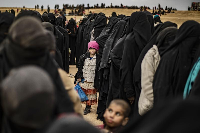 Women and children queue at a screening point after fleeing the Islamic State group's last redoubt in Syria (AFP Photo/Delil SOULEIMAN)