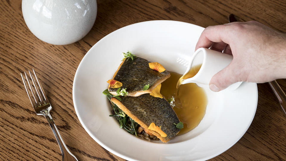 Sunburst trout with trout belly consommé, rye berries, chanterelle mushrooms and kilt greens. - Credit: Ball & Albanese