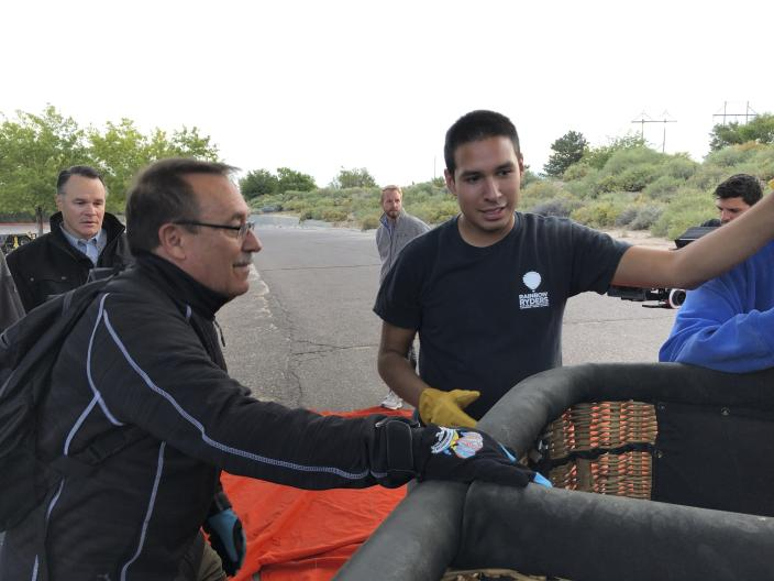 Elijah Sanchez, center, helps passenger board a hot air balloon in Albuquerque, N.M., on Tuesday, Oct. 1, 2019. Sanchez, 20, will be among the youngest pilots to launch as part of this year's Albuquerque International Balloon Fiesta. The nine-day event is expected to draw several hundred thousand spectators and hundreds of balloonists from around the world. It will kick off Oct. 5 with a mass ascension. (AP Photo/Susan Montoya Bryan)