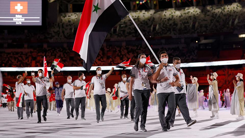 Syria's flag bearers Hend Zaza and Ahmad Saber Hamcho  lead their delegation as they parade during the opening ceremony of the Tokyo 2020 Olympic Games. (Photo by ODD ANDERSEN/AFP via Getty Images)