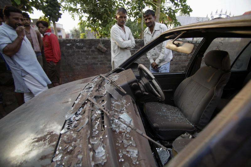 Indian villagers look at an abandoned and damaged car allegedly caused from firing from Pakistan side at Garkhal village near the India-Pakistan international border, 35 kilometers (22 miles) from Jammu, India, Friday, Oct. 25, 2013. An Indian official says at least 10 civilians have been wounded as Pakistani troops fired guns and mortar shells at more than a dozen Indian border posts overnight in the disputed Himalayan region of Kashmir. (AP Photo/Channi Anand)