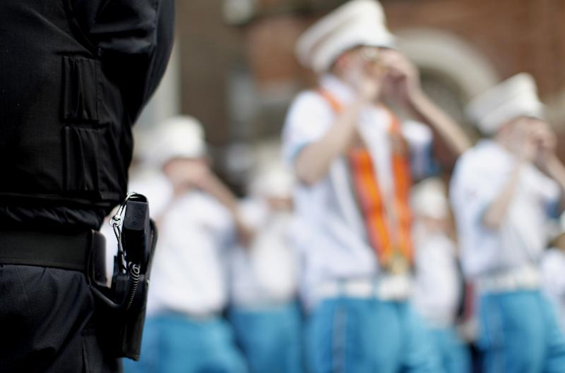 A police service of Northern Ireland officer watching Orange order members passing St Patricks Roman Catholic church in Belfast city centre, Northern Ireland, Saturday, Sept. 29, 2012. Thousands of people are taking part in commemorations in Belfast to mark one of the most significant dates in unionist history. The six-mile march from central Belfast to Stormont marks the 100th anniversary of the Ulster Covenant, to oppose Home Rule for Ireland in 1912. (AP Photo/Peter Morrison)