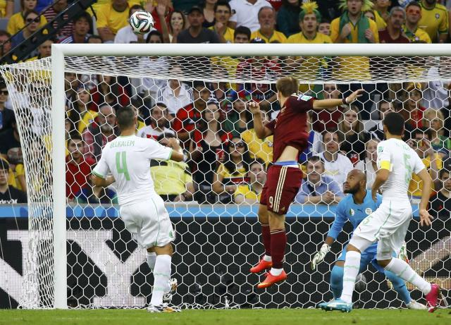 Russia's Alexander Kokorin (C) heads the ball to score past Algeria's goalkeeper Rais Mbolhi (back), Essaid Belkalem (L) and Rafik Halliche (R) during their 2014 World Cup Group H soccer match at the Baixada arena in Curitiba June 26, 2014. REUTERS/Damir Sagolj (BRAZIL - Tags: SOCCER SPORT WORLD CUP TPX IMAGES OF THE DAY)