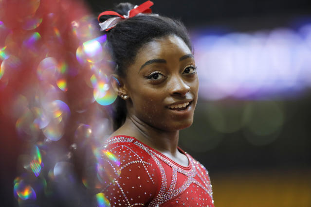 FILE - In this Nov. 2, 2018, file photo, Simone Biles talks to other gymnasts as she warms up on the second and last day of the apparatus finals of the Gymnastics World Championships at the Aspire Dome in Doha, Qatar. With the Olympics a year away, the world's best gymnast believes there's always a new wrinkle, twist or turn to be added to her routine to stay ahead of her competitors. Biles will face some of American challengers in this weekend's GK US Classic, a prelude to next month's Nationals. (AP Photo/Vadim Ghirda, FIle)
