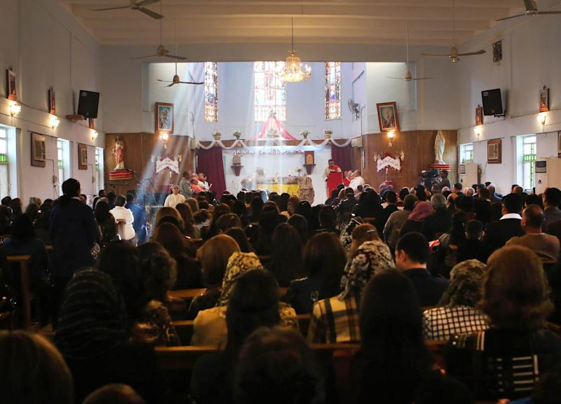 Iraqi Christians attend a Christmas mass at the Mother Teresa Catholic Church in Basra, Iraq's second-largest city, 340 miles (550 kilometers) southeast of Baghdad, Iraq, Wednesday, Dec 25, 2013. Militants on Wednesday launched two separate attacks against Christians in Baghdad, killing more than a dozen people, officials said. (AP Photo/Nabil al-Jurani))