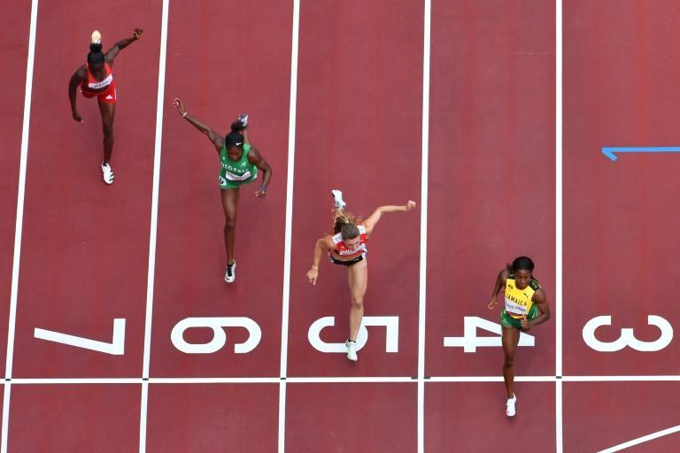An overview shows Jamaica's Shelly-Ann Fraser-Pryce (R) crossing the finish line to win ahead of second-placed Switzerland's Ajla Del Ponte (2R), third-placed Nigeria's Nzubechi Grace Nwokocha (2L) and Gambia's Gina Bass in the women's 100m heats