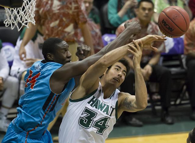 Oregon State forward Daniel Gomis, let, and Hawaii forward Christian Standhardinger (34) reach for a rebound during the first half of an NCAA college basketball game at the Diamond Head Classic on Wednesday, Dec. 25, 2013, in Honolulu. (AP Photo/Eugene Tanner)