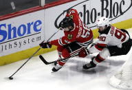 Chicago Blackhawks defenseman Erik Gustafsson, left, controls the puck against New Jersey Devils left wing Marcus Johansson during the second period of an NHL hockey game Thursday, Feb. 14, 2019, in Chicago. (AP Photo/Nam Y. Huh)