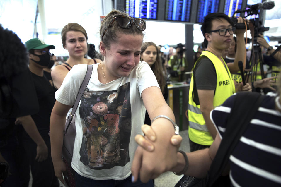 Travelers react as they manage to walk through the protesters to the departure gates during a demonstration at the Hong Kong International Airport in Hong Kong, Tuesday, Aug. 13, 2019. Protesters severely crippled operations at Hong Kong's international airport for a second day Tuesday, forcing authorities to cancel all remaining flights out of the city after demonstrators took over the terminals as part of their push for democratic reforms. (AP Photo/Vincent Thian)