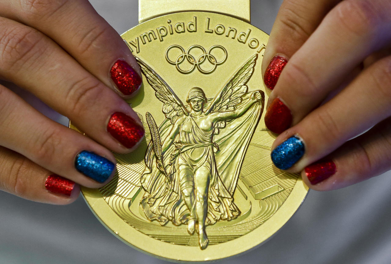 United States' Alex Morgan holds her gold medal during a women's soccer availability following the team's gold medal win at the 2012 Summer Olympics, Friday, Aug. 10, 2012, in London. (AP Photo/Ben Curtis)