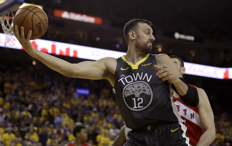 FILE - In this June 7, 2019, file photo, Golden State Warriors center Andrew Bogut (12) holds the ball against the Toronto Raptors during the second half of Game 4 of basketball's NBA Finals in Oakland, Calif. Bogut announced Tuesday, Dec. 1, 2020 that he is calling quits on his bid for an Olympic medal and has decided to retire after 15 years in professional basketball. (AP Photo/Ben Margot, File)