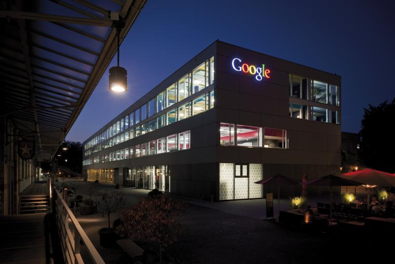 Building with the Google logo lit up at night.