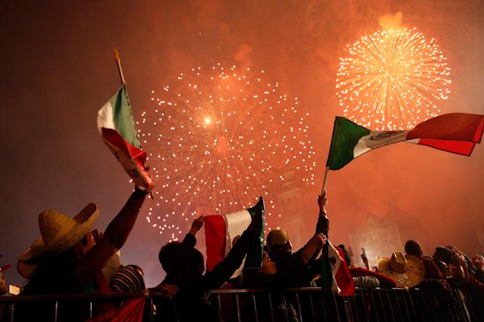 Revelers wave Mexican flags as fireworks explode after President Andres Manuel Lopez Obrador gave the annual independence shout from the balcony of the National Palace to kick off Independence Day celebrations, in Mexico City, Sunday, Sept. 15, 2019.