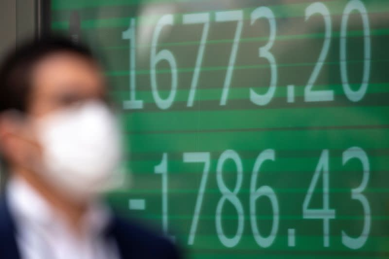 A man wearing a protective face mask walks past a screen showing Nikkei index outside a brokerage in Tokyo
